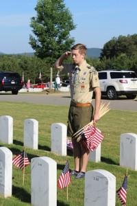 Boy Scout salutes gravestone